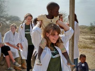 Frivillig som leker med et barn utenfor Medisinplasseringen i Tanzania