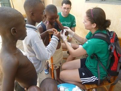 Frivillig leker med barn utenfor en klinikk på medisinprosjektet i Togo