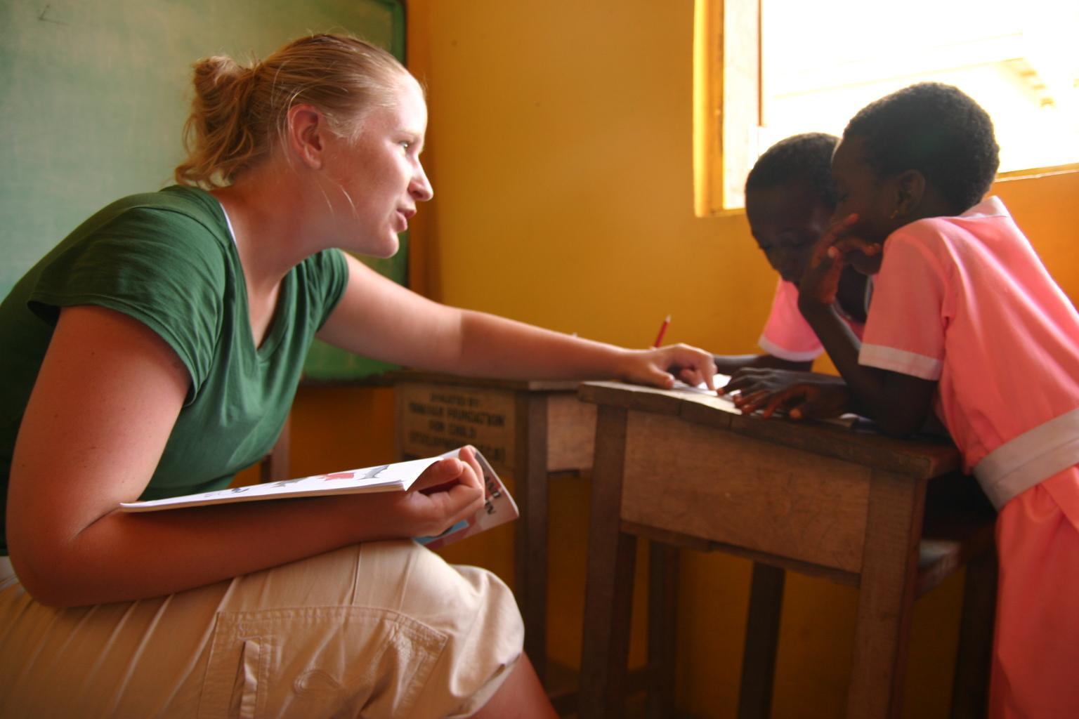 Frivillig hjelper to lokale barn med uttale i Ghana