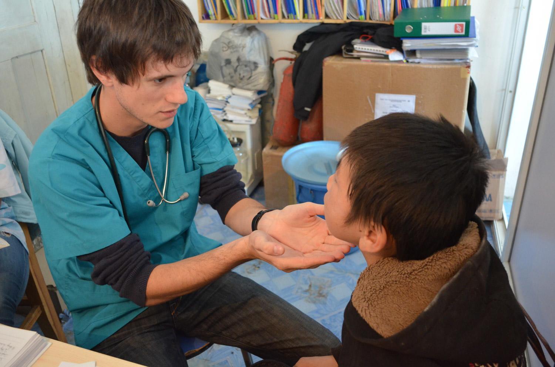 Frivillig på språkterpiprosjektet som jobber med et barn på en klinikk i Marokko