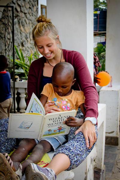 En frivillig leser bok med et av barna på rehabiliteringssenteret på språkterapi i Tanzania