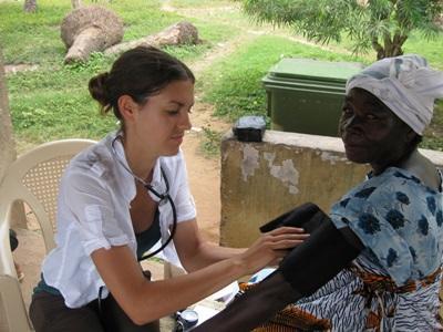 Frivillig sykepleier sjekker blodtrykket til en dame i Ghana