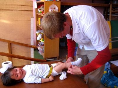 Frivillig på sykepleieprosjektet kler på et barn på en klinikk i Peru
