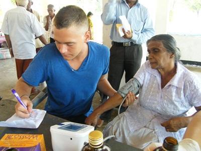 Frivillig sykepleier noterer ned blodtrykket til en eldre dame på et outreachprogram på Sri Lanka