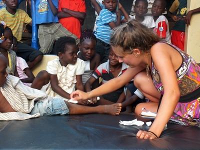 Sykepleiefrivillig renser et barns sår i Togo