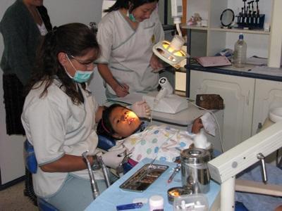 Frivillig på Tannlegefagprosjekt i Bolivia observerer en lokal tannlege som behandler et barn
