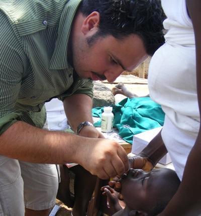 Frivillig gjennomfører tannsjekk på et barn i Ghana