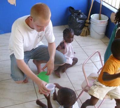 Frivillig på tannlegefagprosjektet på Jamaica mater et barn på en klinikk