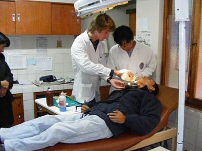 Frivillig på tannlegfagprosjektet som observerer under tannbehandlinger i Peru
