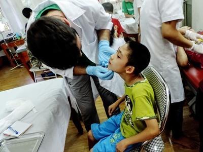 En frivillig undersøker et barn på tannlegefag i Vietnam