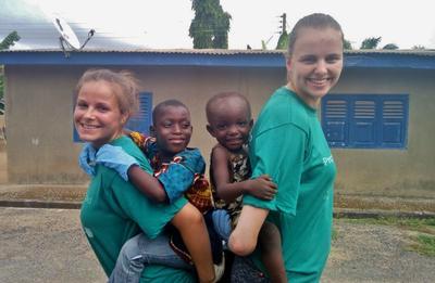 To frivillige med hvert sitt barn på ryggen mens de leker