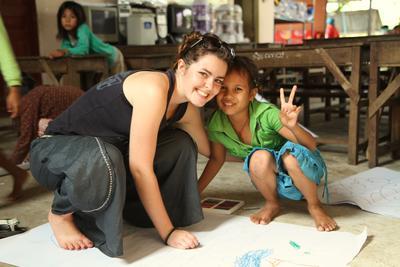 En frivillig tegner sammen med ei ung jente på et dagsenter i Phnom Pehn