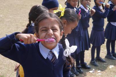 En gruppe barn får undervisning i hvordan man pusser tenner