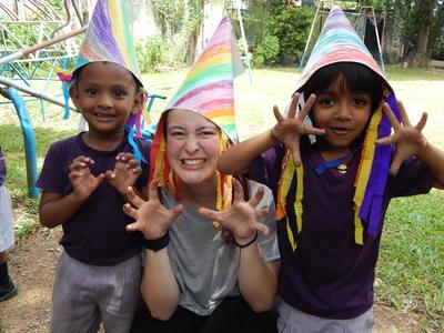 En frivillig leker med to barn fra et dagsenter på Sri Lanka
