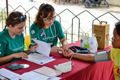 To frivillige måler blodtrykk og noterer resultater, under oppsøkende, medisinsk arbeid
