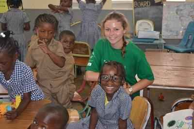 Frivillig-jente sitter sammen med elever på en skole i Tanzania