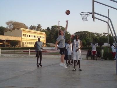 Frivillig basketballtrener som scorer under en trening på en skole i Ghana