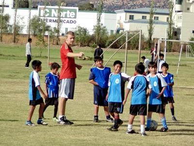Unge bolivianske gutter trener fotball sammen med en frivillig