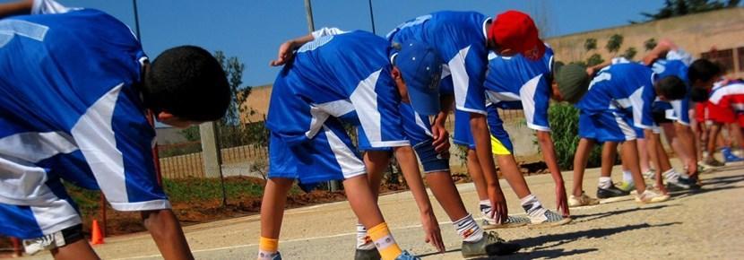Elever på sportprosjektet varmer opp sammen med en frivillig trener før timen