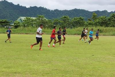Ungdom som trener rugby på en gressbane på Samoa