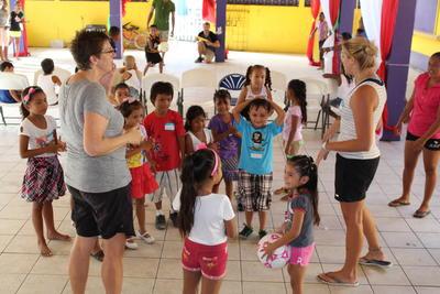Kvinnelig frivillig holder barna I aktivitet med sport