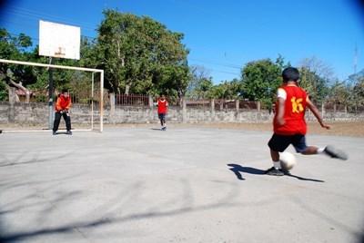 Elev scorer mål på en fotballtrening med en frivillig trener i Costa Rica