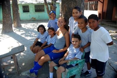 Frivillig fotballtrener tar en pause sammen med spillerne på en skole i Costa Rica, Mellom-Amerika