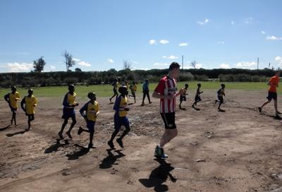 Frivillige varmer opp før trening sammen med barn i Kenya