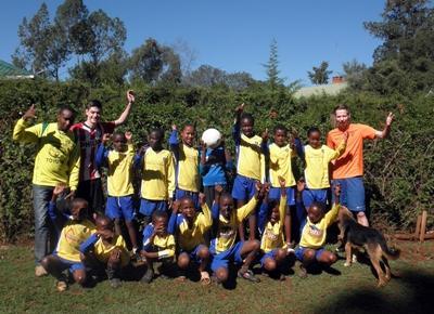 Gruppebilde av frivillige sammen med et fotballag i Kenya