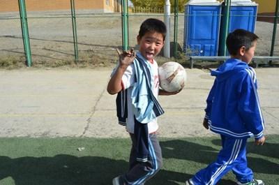 Ung gutt som trener fotball med en frivillig i Mongolia