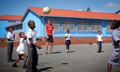 Frivillig sportstrener underviser barn på en skole i Sør-Afrika