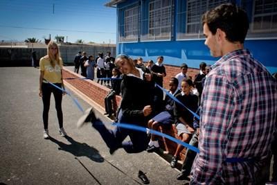 Barn på en skole i Sør-Afrika hopper tau med frivillige trenere