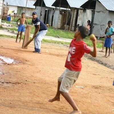 Frivillige trenere spiller cricket med elever på Sri Lanka