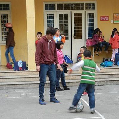 Sportsfrivillig gjør oppvarmingsøvelser med skolebarn i Vietnam