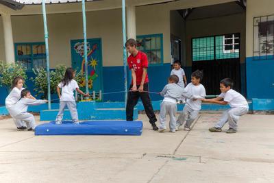 En frivillig organiserer tautrekking med barn på sportsprosjektet i Ecuador