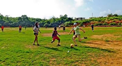 Frivillig som trener fotball med skolebarn i Ghana