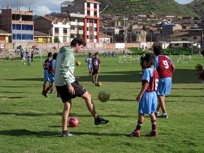 Frivillig som spiller fotball med elever på sportprosjekt i Peru