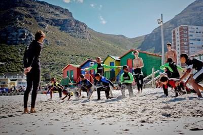 Elever på surfeprosjektet i Sør-Afrika tøyer ut før de går i vannet med frivillige trenere