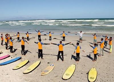 Vanskeligstilte barn strekker ut sammen med frivillige på Surfeprosjektet i Sør-Afrika