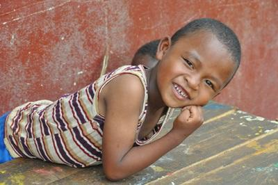 En ung gutt smiler stort til kamerat i Madagaskar