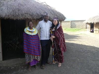 Frivillig som lærer seg swahili sammen med en ansatt og lokal i en tradisjonell landsby