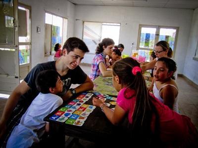 Frivillig på Undervisningsprosjekt hjelper elever med skolearbeid på en skole i Argentina