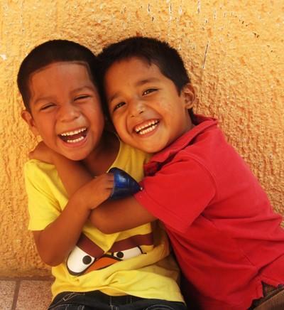 To smilende gutter utenfor en skole i Belize