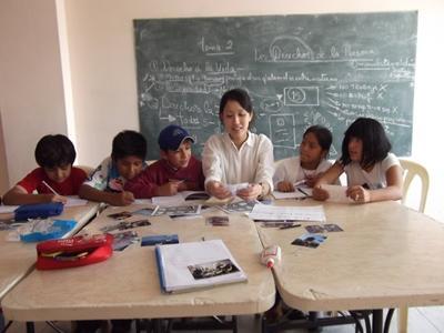 Frivillig lærer jobber med skolearbeid sammen med elever på en skole i Bolivia, Sør-Amerika