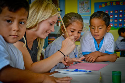 En frivillig hjelper barn med kunstaktiviteter på sommerskolen