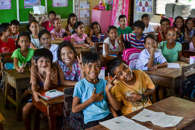 Frivillige innen undervisning assisterer i store klasser på Filippinene