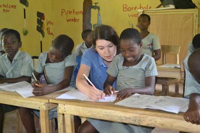 En frivillig hjelper en elev med en skriftlig oppgave
