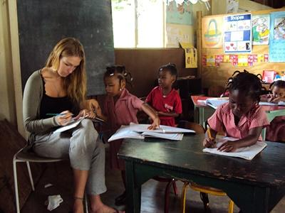 Frivillig lærer retter elevarbeid på en skole på Jamaica