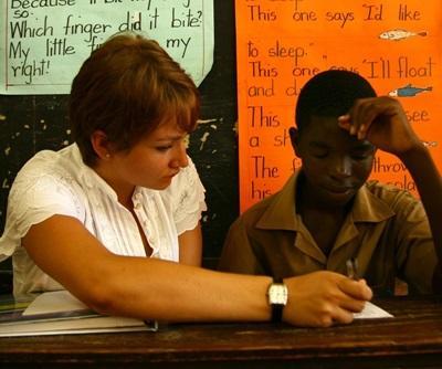 Frivillig veileder en elev i et klasserom på Jamaica