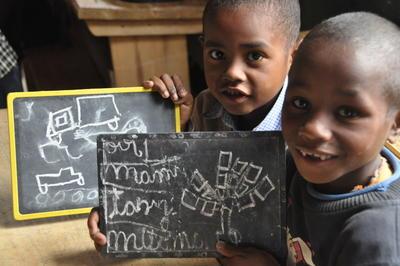 To gutter viser stolt frem tegningene sine på en barneskole på Madagaskar